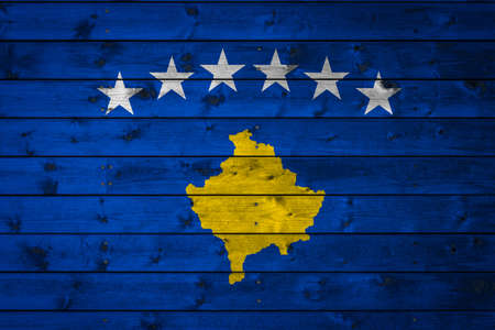 The national flag of Kosovo is painted on a camp of even boards nailed with a nail. The symbol of the country.