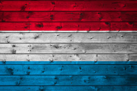 The national flag of Luxembourg is painted on a camp of even boards nailed with a nail. The symbol of the country.