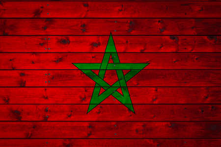 The national flag of Morocco is painted on a camp of even boards nailed with a nail. The symbol of the country. Фото со стока