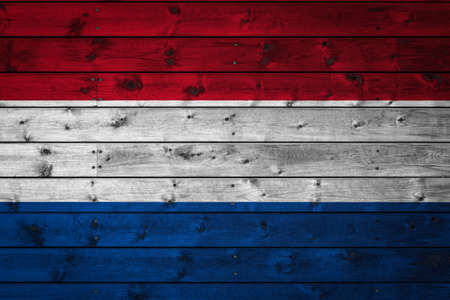 The national flag of Netherlands is painted on a camp of even boards nailed with a nail. The symbol of the country. Фото со стока