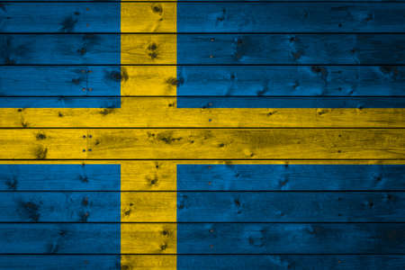 The national flag of Sweden is painted on a camp of even boards nailed with a nail. The symbol of the country.
