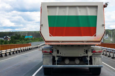 Big truck with the national flag of Bulgaria moving on the highway, against the background of the village and forest landscape. Concept of export-import, transportation, national delivery of goods