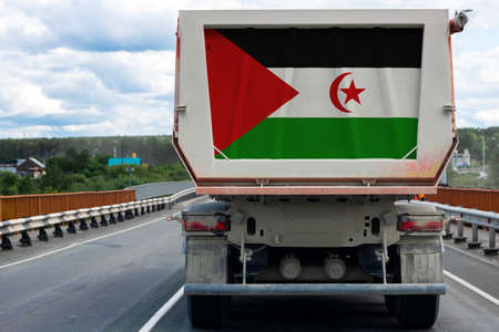 Big truck with the national flag of West Sahara moving on the highway, against the background of the village and forest landscape. Concept of export-import, transportation, national delivery of goods
