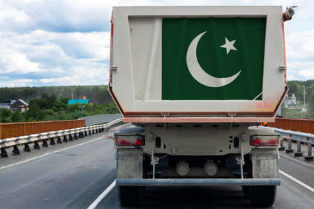 Big truck with the national flag of Pakistan moving on the highway, against the background of the village and forest landscape. Concept of export-import, transportation, national delivery of goods