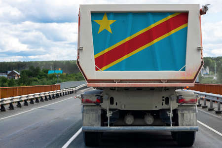 Big truck with the national flag of Democratic Republic of the Congo moving on the highway, against the background of the village and forest landscape. Concept of export-import, transportation, national delivery of goods