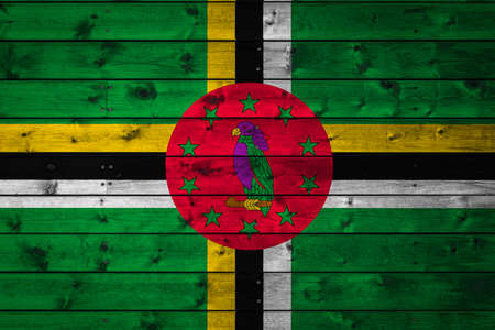 The national flag of Dominica is painted on a camp of even boards nailed with a nail. The symbol of the country. 免版税图像