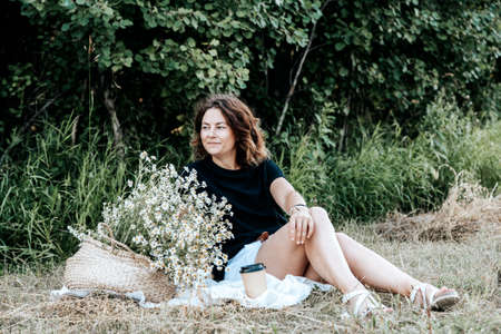 Outdoor fashion portrait of beauty young woman smiling, looking at storoam and a great time at a makeshift picnic on nature. Summer clothing and accessories. 스톡 콘텐츠