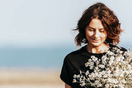 Portrait joyful young woman brunette in black t-shirt with a bouquet of daisies having fun, smile and enjoy day on field. stylish hipster woman.Outdoor atmospheric lifestyle photo