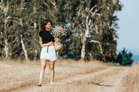 A dark-haired woman smiles, walks along the road in field dressed in a romantic clothers holding wicker bag with a bouquet chamomile on a summer day. Concept of summer holidays in village and live style 스톡 콘텐츠
