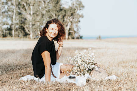 Portrait joyful young woman brunette in black t-shirt with a bouquet of daisies resting on a blanket among beautiful nature on field. Stylish hipster woman.Outdoor atmospheric lifestyle photo 스톡 콘텐츠