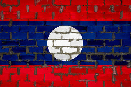 The national flag of Laos painted on a wall of sibit blocks with cement. The symbol of the country. 스톡 콘텐츠