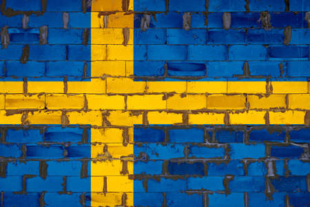 The national flag of Sweden painted on a wall of sibit blocks with cement. The symbol of the country. 스톡 콘텐츠