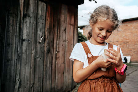 A girl takes care of the newly born yellow chickens in yard. Small home farm and petting zoo concept 스톡 콘텐츠