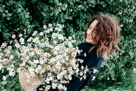 Portrait joyful young woman brunette in black t-shirt with a bouquet of daisies having fun, smile and enjoy day on forest. stylish hipster woman.Outdoor atmospheric lifestyle photo