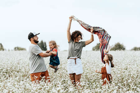 Happy family walking in field, playing and enjoying summer day. Livestyle walking concept