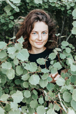 Portrait joyful young woman brunette in black t-shirt in the green foliage of a young tree on the background of the forest. smile and enjoy day on field. stylish hipster woman.Outdoor atmospheric lifestyle photo 스톡 콘텐츠