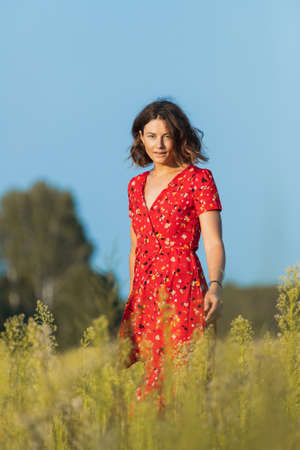 A romantic walk of a curly-haired girl in a red long dress along fields. The concept of female freedom, emancipation and love