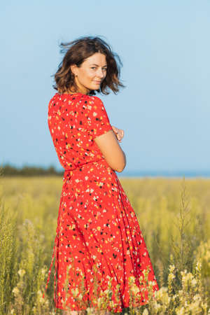 Portrait of a beautiful young model in red dress holding a enjoy day, on background field in sunny autumn day. The concept of the unity of women and nature, peaceful mood, eco-friendly life 스톡 콘텐츠