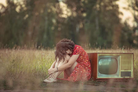 Atmospheric portrait of a brooding young woman in a red dress sitting near an old retro TV in nature. The concept of female freedom and emancipation. Concept of female loneliness and thoughtfulness