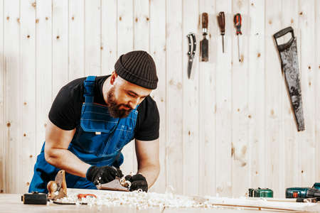 A dark-haired man with a beard and in overalls treating a wooden bar with a black jack plane, in the background a lot of wooden boards. Work with wooden. 写真素材