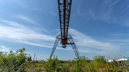 Large metal gantry cranes at a construction site against the blue sky. Type of bearing metal structures of gantry crane for loading goods Фото со стока