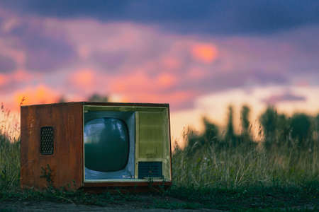 old retro TV set on a field road against a wheat background under the rays of the setting sun Фото со стока