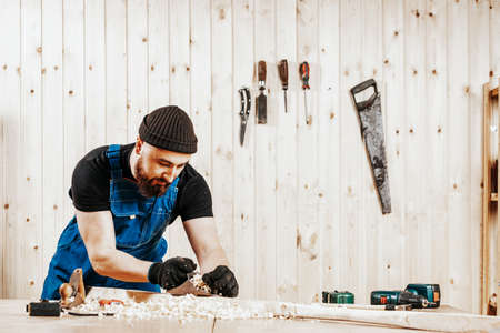 A dark-haired man with a beard and in overalls treating a wooden bar with a black jack plane, in the background a lot of wooden boards. Work with wooden. Фото со стока