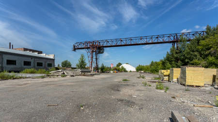 Novosibirsk / Russia - July 25 2020: large metal gantry crane at a construction site, in the background industrial warehouses for storing goods. Type of bearing metal structures of gantry crane against the blue sky