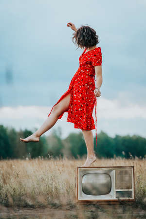 Atmospheric portrait of a young woman in a red dress walking on an old retro TV in nature. The concept of female freedom and emancipation