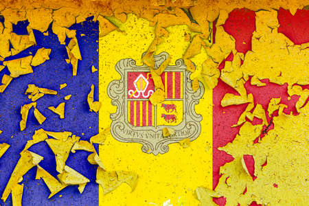 The national flag of Andorra is painted on an old metal wall with ragged paint. Country symbol. Фото со стока