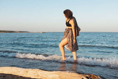 A cheerful dark-haired woman smiles, walks along the beach, kicks waves and enjoys the bright sun on a summer day. Concept of summer holidays at sea and live style