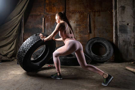 A sporty woman in a pink top and leggings doing sit-ups, pushes weight tire in the sports gym garage. Technique of squats with weight