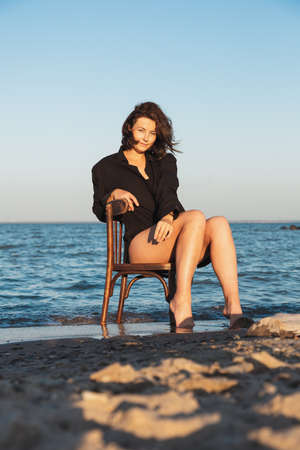 Atmospheric portrait of a young woman in stylish clothers on chair on a sandy beach near a blue sky on a summer daysitting on chair in nature. The concept of female freedom and emancipation Banque d'images