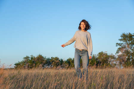 Pretty fresh young woman walking outdoors in the yellow field and wearing sweater and jeans .Concept of summer holidays at village and live style