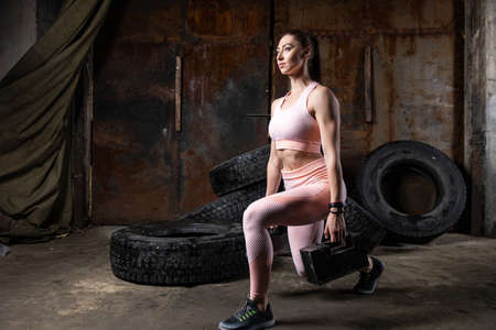 A dark-haired woman coach in a sporty pink short top and gym leggings doing exercise with dumbbell in an old garage, against the background of tires. Conceptual Sports Photo Фото со стока