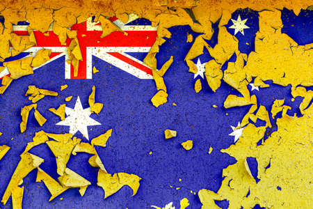 The national flag of Australia is painted on an old metal wall with ragged paint. Country symbol.