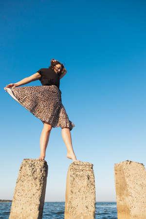 Young beautiful woman in a light casual dress walking on rocks on a sandy beach near a blue sky on a summer day, beautiful sea against a blue sky Фото со стока