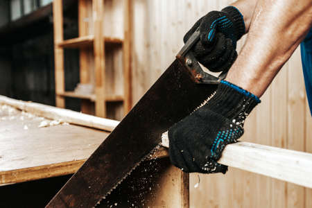 close-up of a man construction worker sawing a block of wood with a hand saw in a workshop Фото со стока