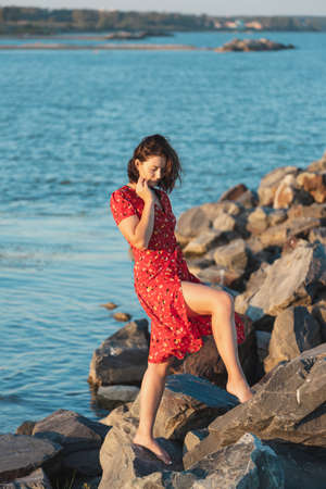Young beautiful woman in a light casual red dress resting and posing on rocks on a sandy beach near a blue sky on a summer day, beautiful sea against a blue sky Фото со стока