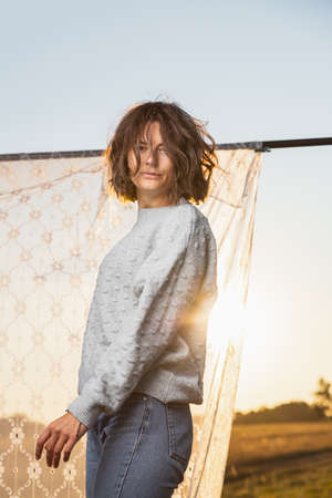 A romantic walk of a curly-haired woman against the background of the a rack with sunset, white curtains, field. The concept of female freedom, emancipation and love