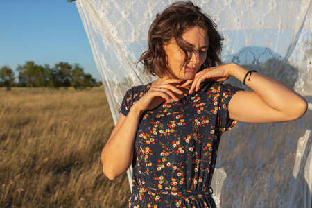 A romantic walk of a curly-haired woman in a dress against the background of the a rack with white curtains, field. The concept of female freedom, emancipation and love