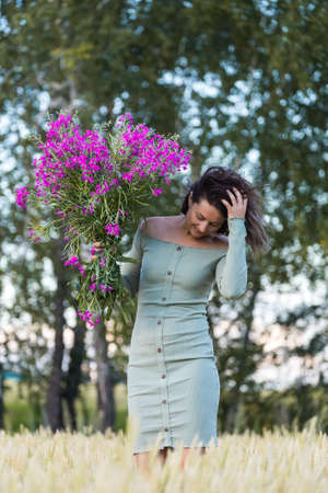 Portrait of a beautiful woman with a bouquet of flowers walking in the fields, in background field and forest. The concept of the unity of women and nature, peaceful mood, eco-friendly life