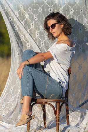 Pretty fresh young woman sitting on chair outdoors in field and wearing in dress in the background a rack with white curtains .Concept of summer holidays at village and live style Фото со стока