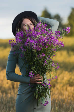 Portrait of a beautiful woman with a bouquet of flowers walking in the fields, in background field. The concept of the unity of women and nature, peaceful mood, eco-friendly life