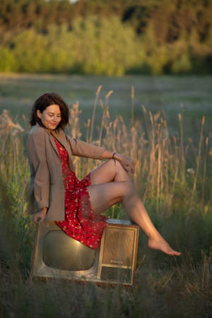 Atmospheric portrait of a young woman in a red dress sitting on an old retro TV in nature. The concept of female freedom and emancipation
