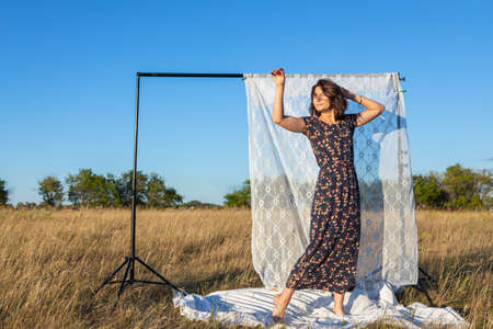 Pretty fresh young woman posing outdoors in field and wearing in dress in the background a rack with white curtains. Concept of summer holidays at village and live style