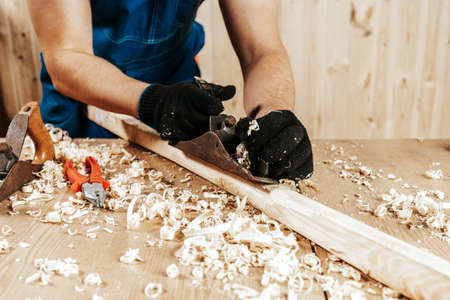 Close up of the man in overalls treating a wooden bar with a black jack plane, in the background a lot of wooden boards. Work with wooden. Фото со стока
