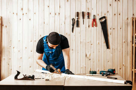 A young brunette man builder handles a wooden bar with a black jack plane in the workshop, in the background a lot of wooden boards and tools