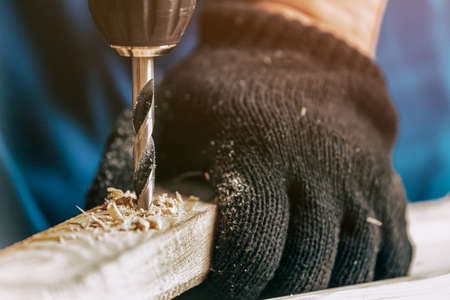 Close-up of a male construction worker in a black dirty construction overall closes a screw with a black modern screwdriver in a wooden block in the workshop Imagens