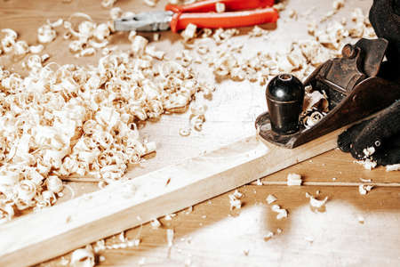Close up of the a young brunette man builder handles a wooden bar with a black jack plane in the workshop, in the background a lot of wooden boards and tools